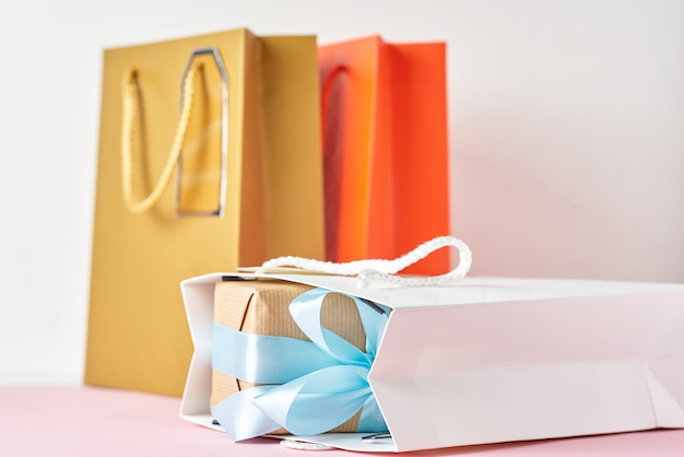 Colorful paper shopping bag and gift box with blue ribbon on a white