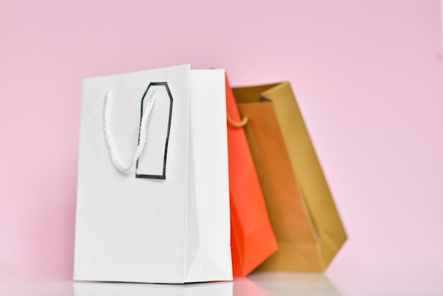 Colorful paper shopping bag on a pink surface