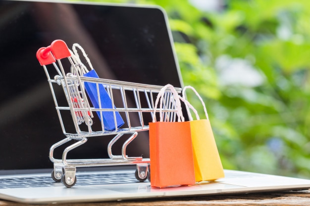 Colorful paper shopping bag in trolley on laptop