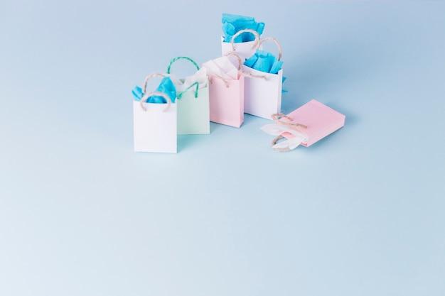 파란색 배경에 고립 된 다채로운 종이 쇼핑백
