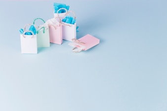 Colorful paper shopping bags on blue surface
