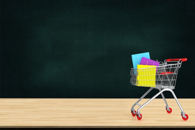 Colorful paper shopping bags in trolley on wood table with black board backdrop