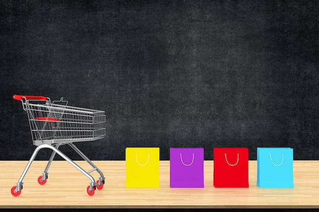 Colorful paper shopping bags with trolley on wood table with black board backdrop