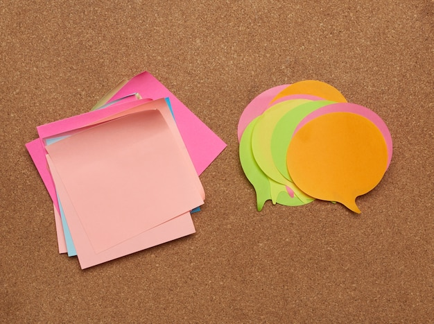 Colorful paper stickers glued on brown balsa board, idea and multitasking, close up