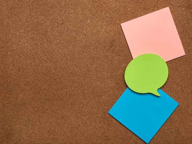 Colorful paper stickers glued on brown board, idea and multitasking, close up, copy space