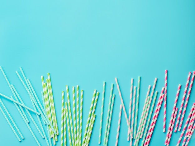 Colorful paper straws on blue background. ecology product. equipment for single use.