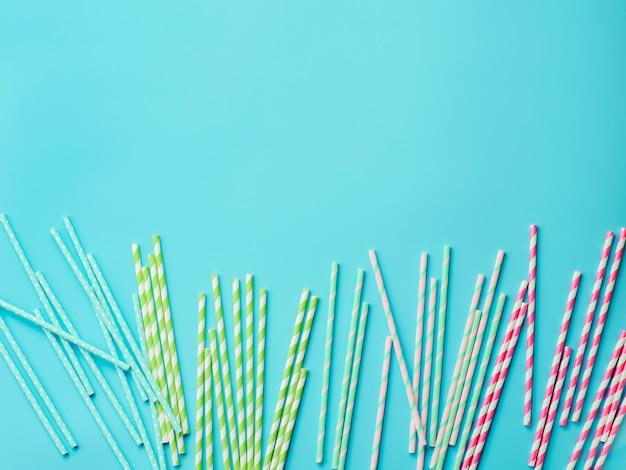 Красочные бумажные соломинки на синем фоне. экологический продукт. оборудование для одноразового использования.