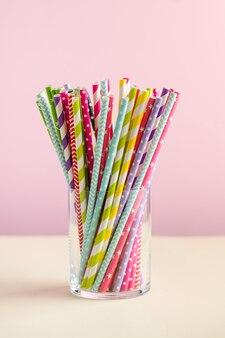 Разноцветные бумажные тубы для напитков в стакане на цветных поверхностях