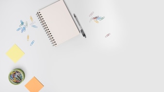 Colorful paperclips; spiral notebook; pen; adhesive note on white background