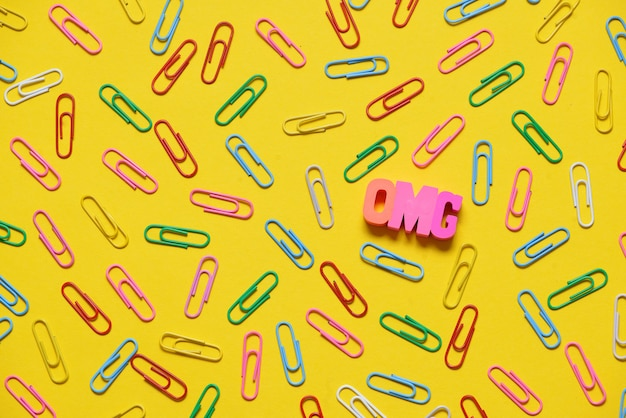 Colorful paperclips on yellow background and omg letters
