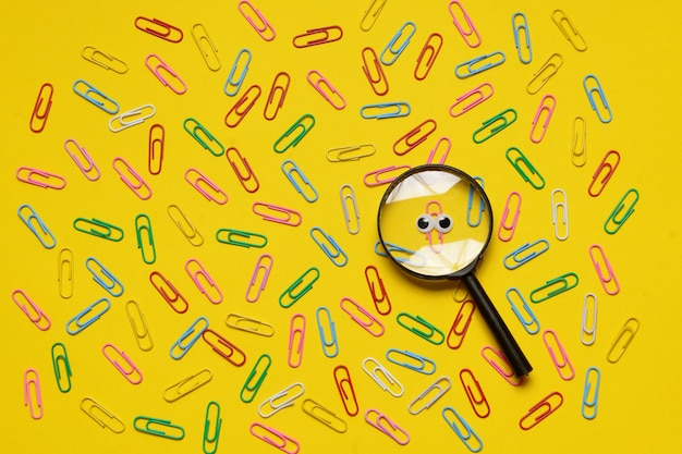 Colorful paperclips on yellow background and only one under magnifying glass
