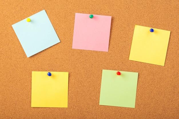 갈색 코르크 보드 배경에 압정으로 고정 된 다채로운 논문.