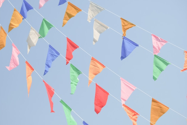 Colorful party flags bunting hanging on blue sky for holiday decoration