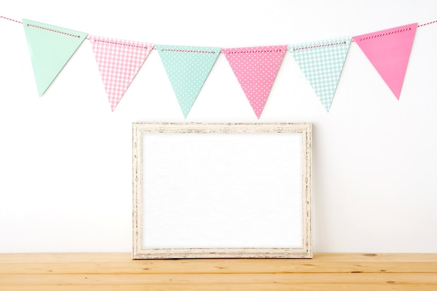 Colorful party flags hanging over blank white vintage wooden frame