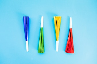 Colorful party horn blower on blue background