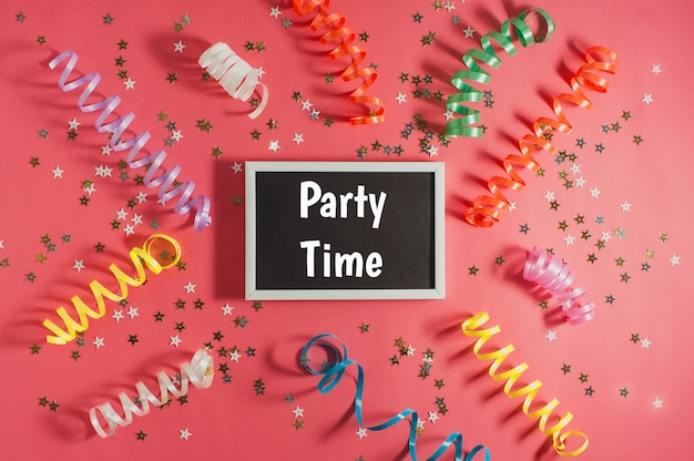 Colorful party streamers, gold little stars and blackboard for text on red backgrond. party or birthday concept.