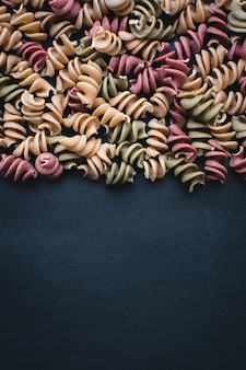 Colorful pasta fusili detail on a black background