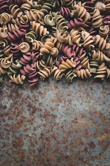 Colorful pasta fusili detail on a rusty metallic background