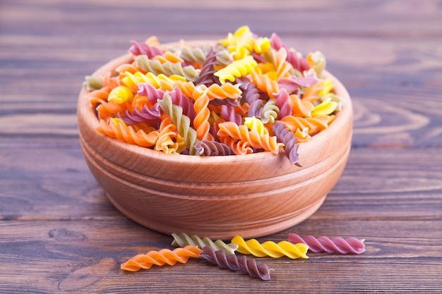 Colorful pasta fusilli with spinach, carrots, beets in a wooden bowl on a dark table