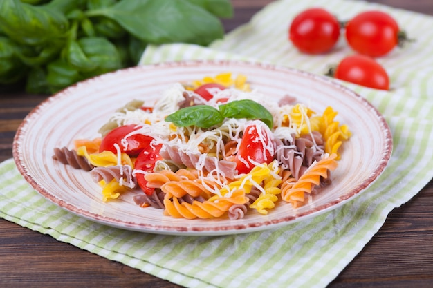 Colorful pasta fusilli with tomato, basil and cheese on a dark wooden table