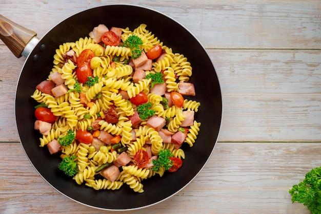 カラフルなパスタロティーニ、チェリートマト、ハムを鍋に。閉じる。上面図。