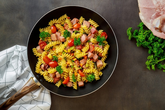 Colorful pasta rotini, cherry tomatoes and ham on pan.