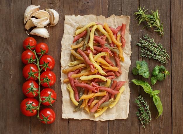 カラフルなパスタ、野菜、ハーブの木製テーブルトップビュー