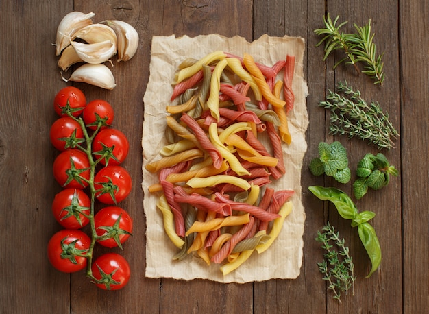 Colorful pasta, vegetables and herbs on a wooden table  top view