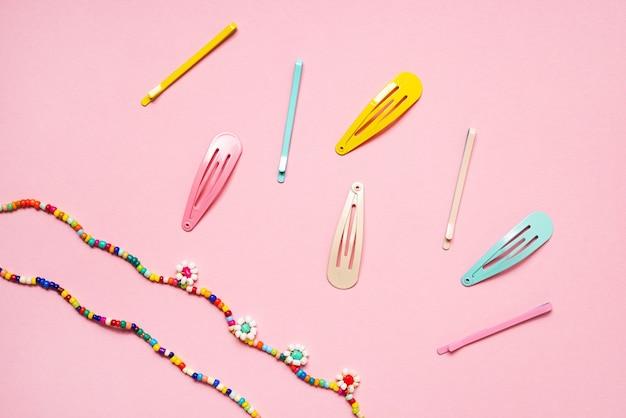 ピンクの背景にカラフルなパステルアクセサリーのヘアピンは、過去からトレンディなモダンをクローズアップ