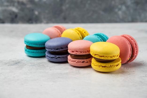 Macarons pastello colorato alle mandorle sul tavolo bianco.