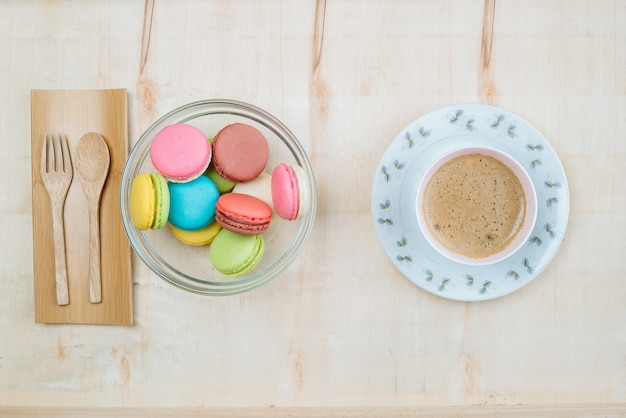 Colorful pastel cake macaron with coffee background from above