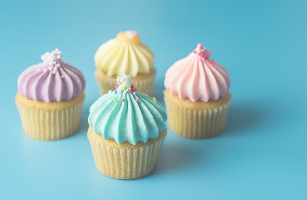 Colorful pastel cupcake on blue pastel background with blue cupcake on focus