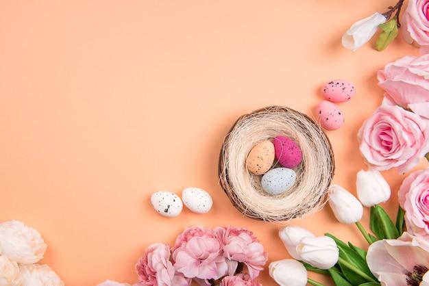Красочные пастельные пасхальные украшения с яичным гнездом и весенними цветами на светло-оранжевом фоне