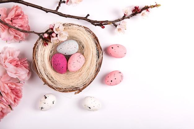 Красочные пастельные пасхальные украшения с яйцом и весенними цветами на белом фоне, вид сверху