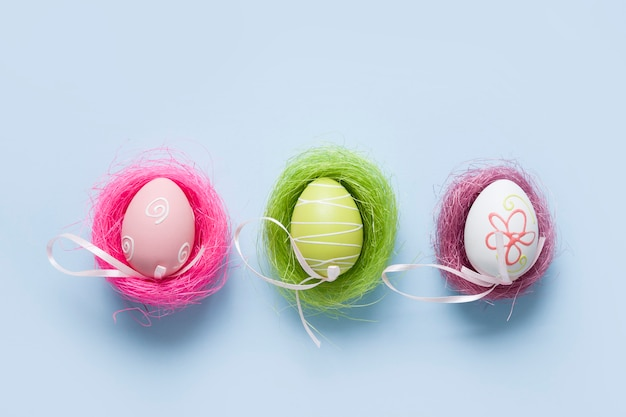 Colorful pastel eggs in three nests. easter minimal creative composition on blue. happy holiday.