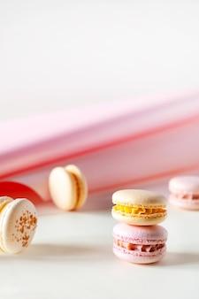 Красочные пастельные французские миндальное печенье или миндальное печенье на белом и розовом фоне