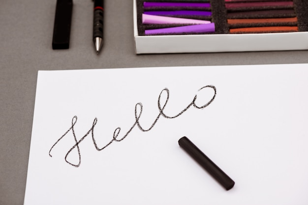 Colorful pastel, pen, paper with word hello on grey table