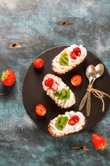 Colorful pastry cakes with chantilly cream, fruits and berries on grunge blue wooden background