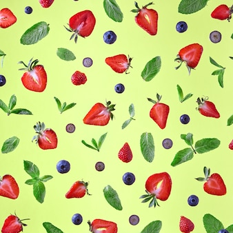 Colorful pattern from mint leaves, strawberry and blueberries