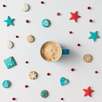Красочный узор из рождественского печенья и красных ягод с чашкой кофе