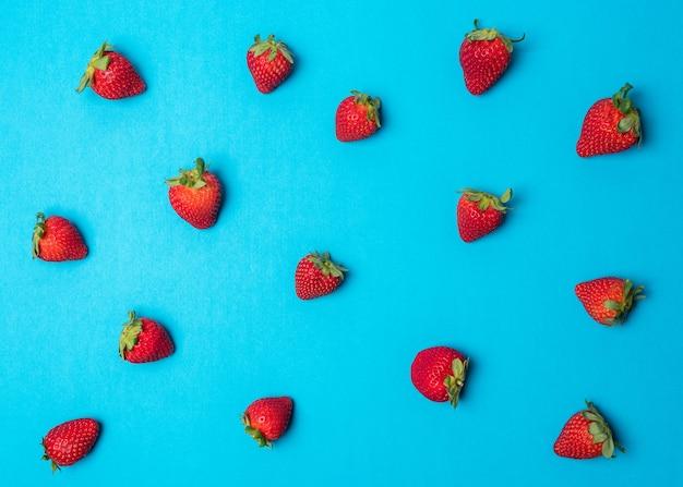 鮮やかなブルーの表面にイチゴで作られたカラフルなパターン。