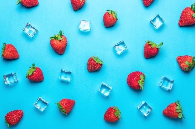 青い表面に角氷が付いているイチゴで作られたカラフルなパターン。