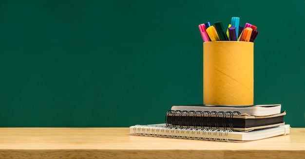 Colorful pen in box on stack of study notebook on wooden table with blackboard wall