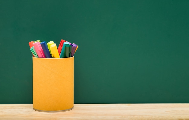 Colorful pen box on table with green blackboard wall