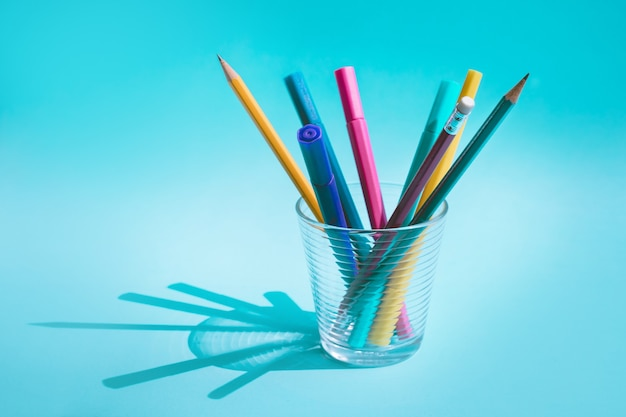 Colorful pen and pencil in glass with long shadow on pastel background