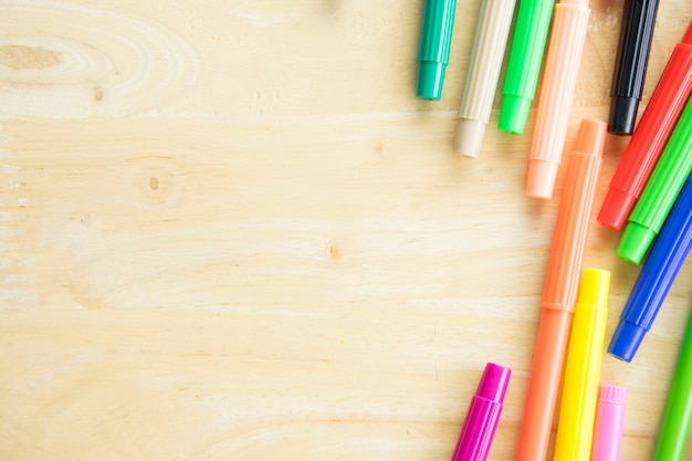 Colorful pen on wooden table background with space.