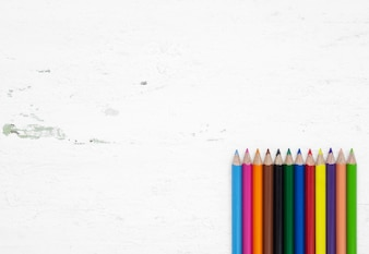 Colorful pencil crayons on a grunge white wood background with blank space