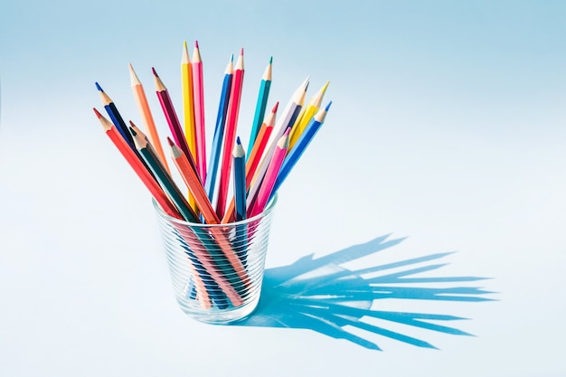 Colorful pencil in glass cup with long shadow