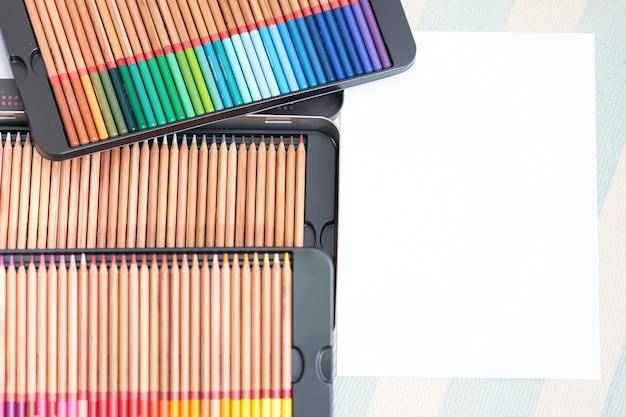 흰 종이와 바닥에 상자에 다채로운 연필