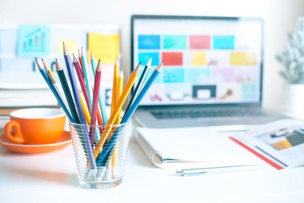 홈 오피스의 책상 테이블에 유리에 다채로운 연필
